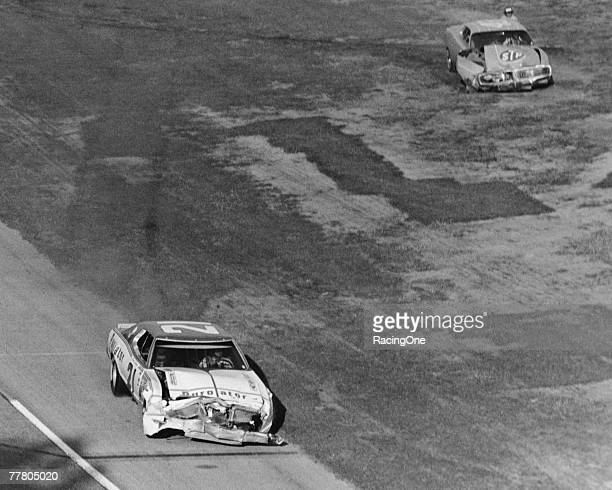 David Pearson driver of the Wood Brothers Mercury drives towards the finish line as Richard Petty driver of the STP Dodge sits in the infield after...
