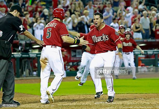 David Peralta and Ender Inciarte of the Arizona Diamondbacks celebrate as they score on teammate Paul Goldschmidt's game winning walk-off double...
