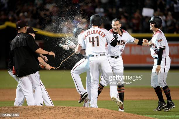 David Peralta of the Arizona Diamondbacks celebrates with teammates after a bases loaded walk in the ninth inning to score the winning run against...