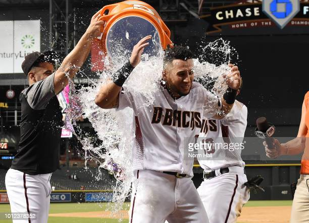 David Peralta of the Arizona Diamondbacks gets showered with ice water after hitting the game winning home run in the fourteenth inning against the...