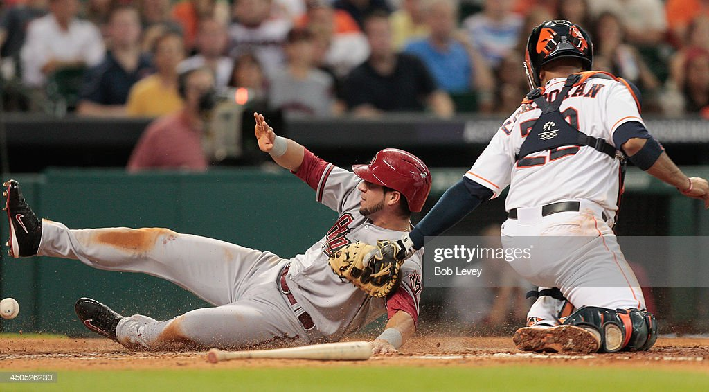 David Peralta #6 of the Arizona Diamondbacks scores in the third inning as Carlos Corporan #22 of the Houston Astros can't handle the throw at Minute Maid Park on June 12, 2014 in Houston, Texas.