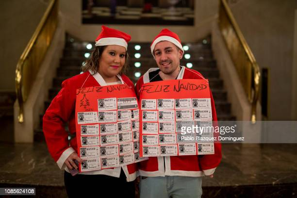 David Perez and Antonia Mendez dressed as Santa Claus pose for a portrait before the draw of Spain's Christmas lottery named 'El Gordo' at the Teatro...