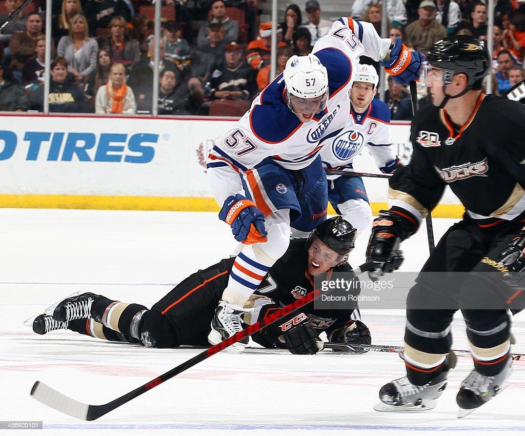 David Perron #57 of the Edmonton Oilers stumbles over Hampus Lindholm #47 of the Anaheim Ducks on December 15, 2013 at Honda Center in Anaheim, California.
