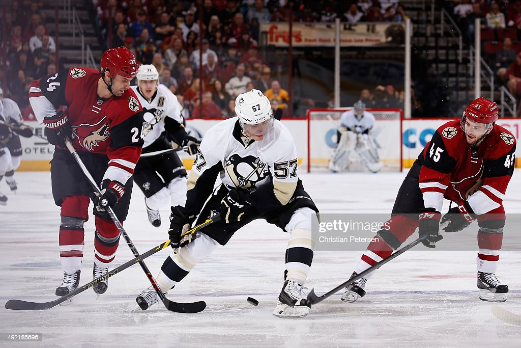 David Perron #57 of the Pittsburgh Penguins battles for loose puck with Kyle Chipchura #24 and Stefan Elliott #45 of the Arizona Coyotes during the first period of the NHL game at Gila River Arena on October 10, 2015 in Glendale, Arizona.
