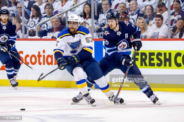 David Perron of the St Louis Blues and Mark Scheifele of the Winnipeg Jets chase the loose puck during first period action in Game Five of the...