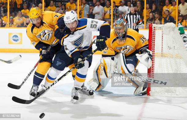 David Perron of the St Louis Blues battles for the puck against Yannick Weber of the Nashville Predators in front of goalie Pekka Rinne in Game Three...