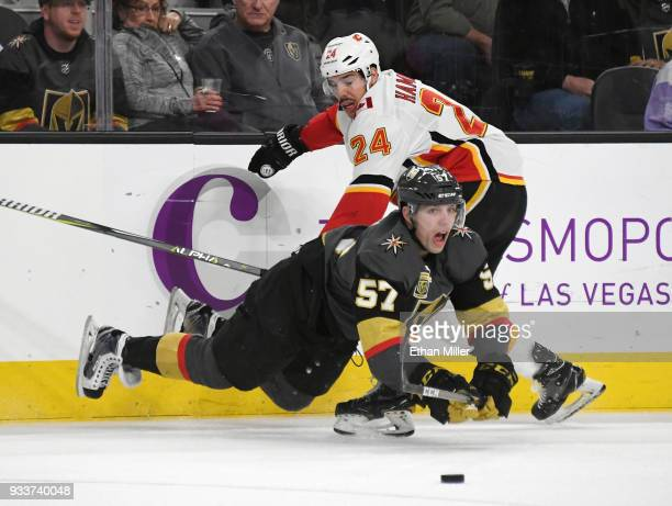 David Perron of the Vegas Golden Knights falls to the ice as he goes after the puck against Travis Hamonic of the Calgary Flames in the first period...