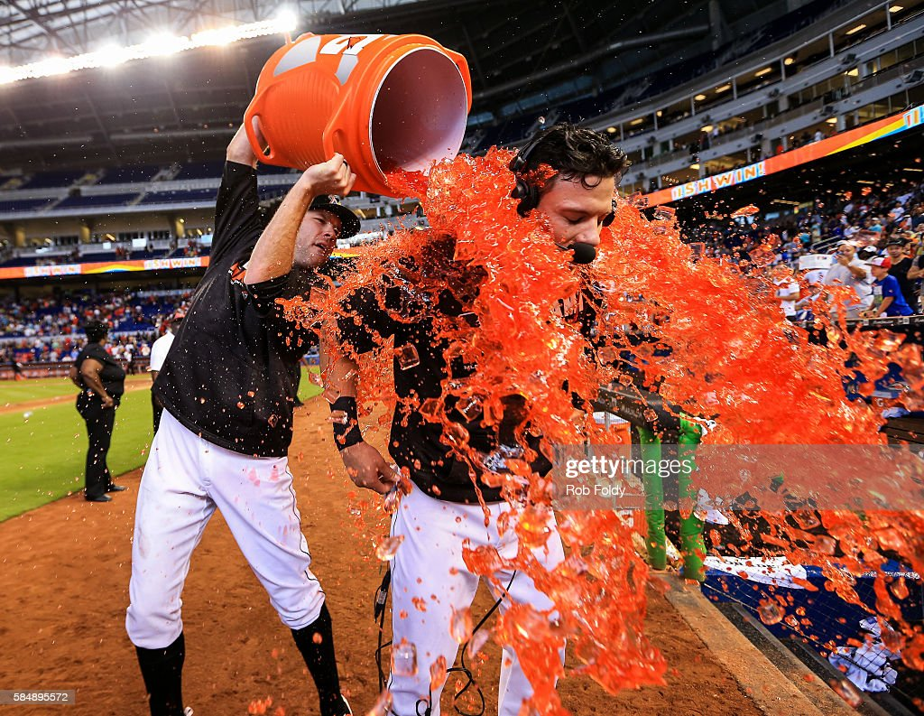 David Phelps #35 dumps sports drink on Derek Dietrich #32 after Dietrich hit a walk-off triple during the ninth inning to end the game against the St. Louis Cardinals at Marlins Park on July 31, 2016 in Miami, Florida.