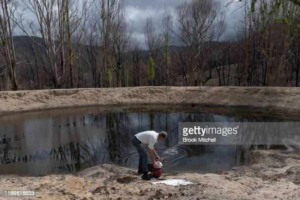 David Pieters tries to pull a blackened water pump from his dam on January 14 2020 in Wytaliba Australia David Pieters' home was nicknamed the...