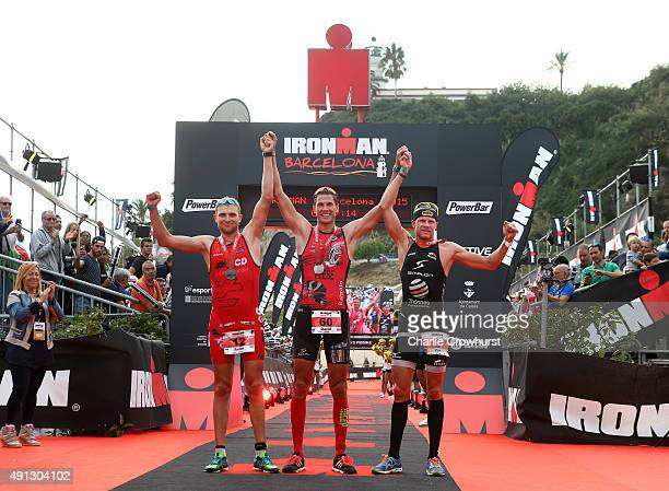 David Plese of Slovenia celebrates after winning the mens race with second place Anton Blokhin of Ukraine and Per Bittner of Germany during Ironman...