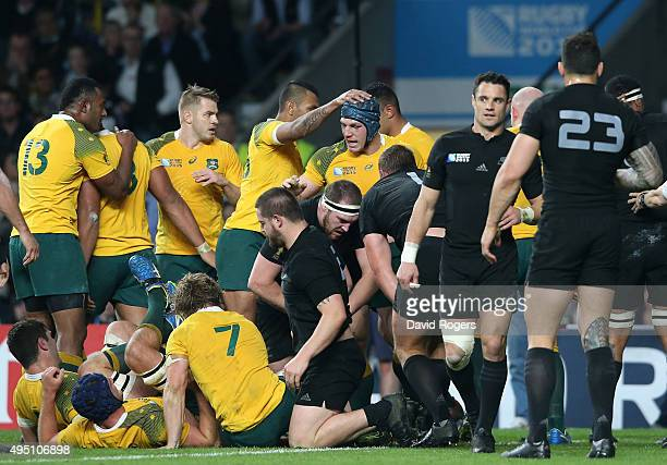 David Pocock of Australia is congratulated by his teammates after scoring his team's first try during the 2015 Rugby World Cup Final match between...