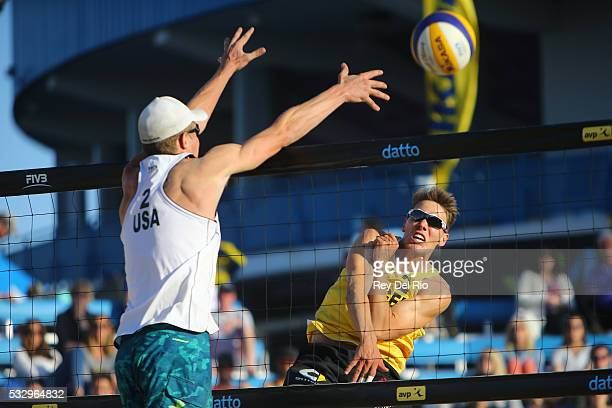 David Poniewaz of Germany hits the ball over the net against Robbie Page of the USA during day 3 of the 2016 AVP Cincinnati Open on May 19 2016 at...