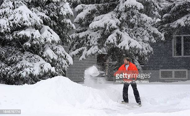 David Post works to clear his driveway as spring snow continues to fall Monday afternoon on March 25 in west Anchorage Alaska Some Anchorage...