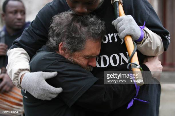 David Pott and Monette Tapa Mekomou embrace besides the Buxton Memorial in Victoria Tower Gardens, Westminster, central London, as they join a Walk...