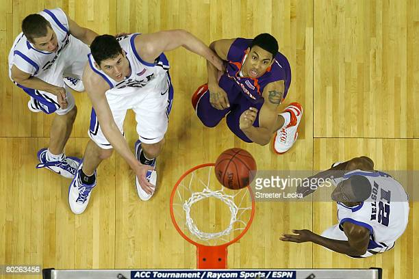 David Potter of the Clemson Tigers and Jon Scheyer Brian Zoubek and DeMarcus Nelson of the Duke Blue Devils look at the ball on the rim during the...