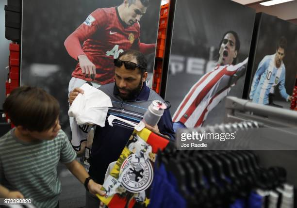 David Prego and his father Rodrigo Prego shop at the Soccer Locker store for German soccer team items as they prepare to show their support for their...