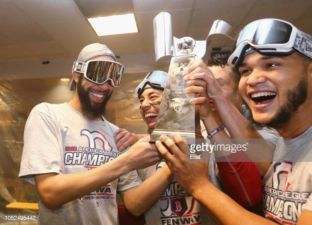 David Price Mookie Betts and Eduardo Rodriguez of the Boston Red Sox celebrate with the William Harridge Trophy in the clubhouse after defeating the...