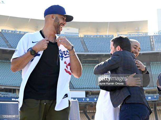 David Price of the Los Angeles Dodgers buttons his new jersey as general manager Andrew Friedman embraces Mookie Betts#50 as they are introduced at a...