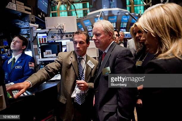 David Pyott chairman and chief executive officer of Allergan Inc center right talks with trader Christopher Trotta center left on the floor of the...
