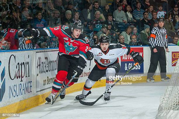 David Quenneville of the Medicine Hat Tigers keeps his eye on the puck as he checks Cal Foote of the Kelowna Rockets behind the net during second...