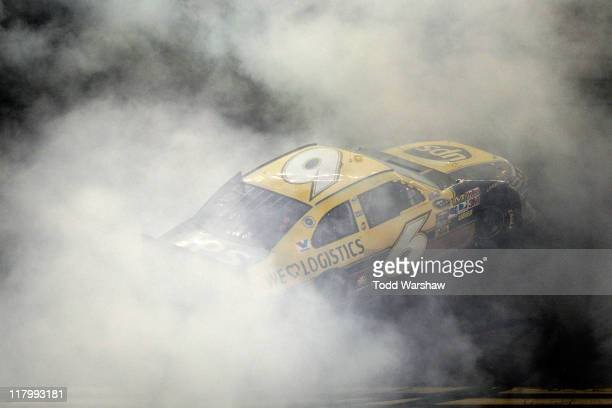 David Ragan driver of the UPS Ford performs a burnout in celebration of winning the NASCAR Sprint Cup Series Coke ZERO 400 Powered by CocaCola at...