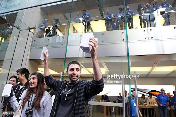 David Rahimi center and Jasmine Juan to his left both from California hold their newly purchased iPhone 6 and iPhone 6 Plus smartphones as they exit...