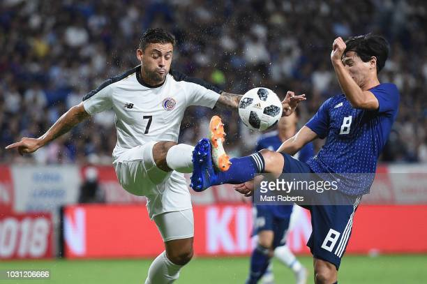 David Ramirez of Costa Rica competes for the ball against Takumi Minamino of Japan during the international friendly match between Japan and Costa...