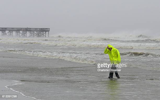 David Reedy of Wilkes County, N.C., walks from the surf created by Hurricane Matthew near the pier on the Isle of Palms in South Carolina on...
