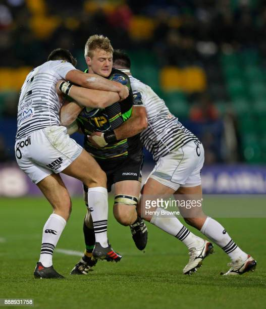 David Ribbans of Northampton Saints tackled by Owen Watkin of Ospreys and Scott Baldwin of Ospreys during the European Rugby Champions Cup match...