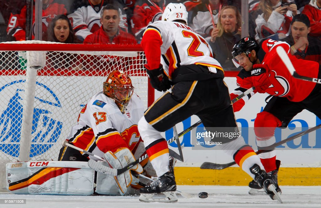 David Rittich #33 and Dougie Hamilton #27 of the Calgary Flames defends the net in the third period against Travis Zajac #19 of the New Jersey Devils on February 8, 2018 at Prudential Center in Newark, New Jersey.