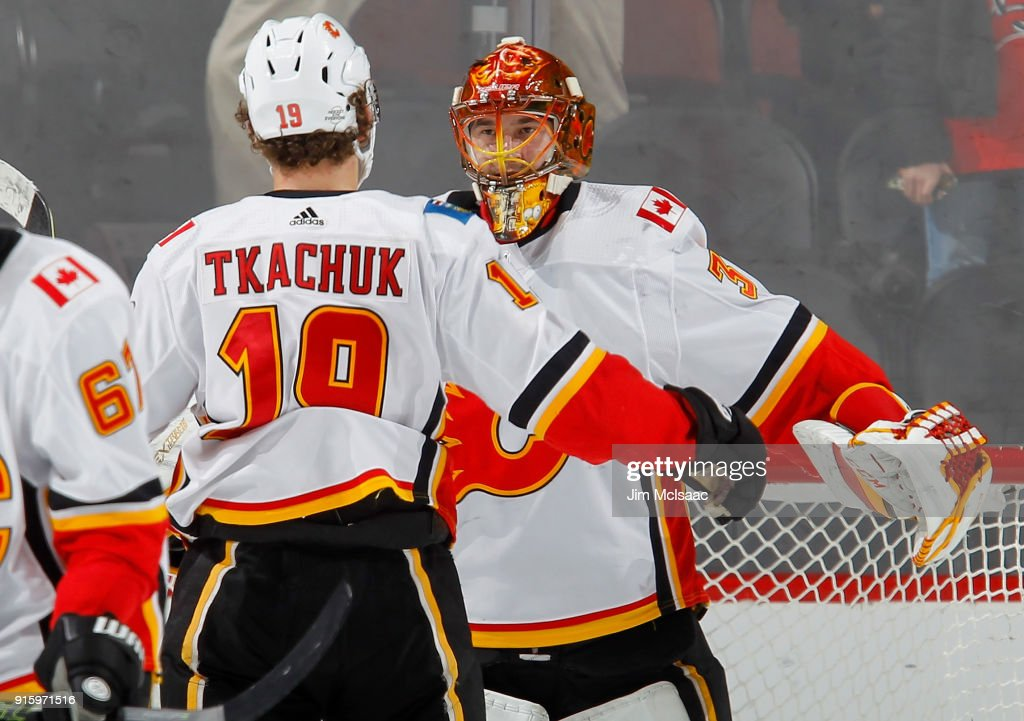 David Rittich #33 and Matthew Tkachuk #19 of the Calgary Flames celebrate after defeating the New Jersey Devils on February 8, 2018 at Prudential Center in Newark, New Jersey.