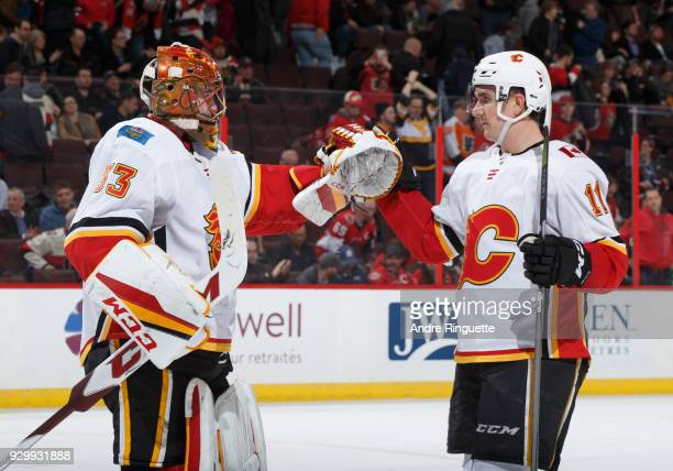 David Rittich and Mikael Backlund of the Calgary Flames celebrate their win over the Ottawa Senators at Canadian Tire Centre on March 9 2018 in...