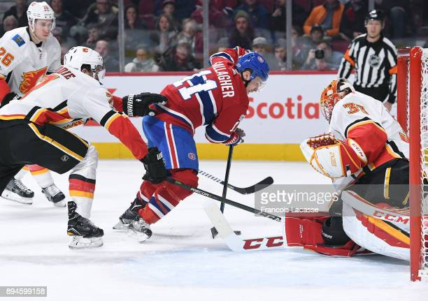 David Rittich and TJ Brodie of the Calgary Flames defend the net against Brendan Gallagher of the Montreal Canadiens in the NHL game at the Bell...