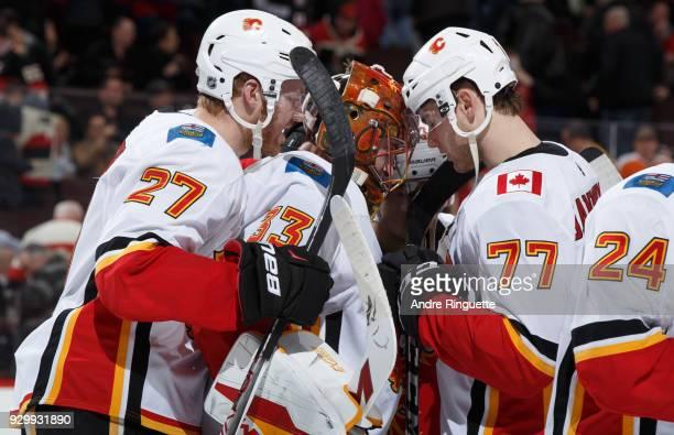David Rittich Dougie Hamilton and Mark Jankowski of the Calgary Flames celebrate their win over the Ottawa Senators at Canadian Tire Centre on March...