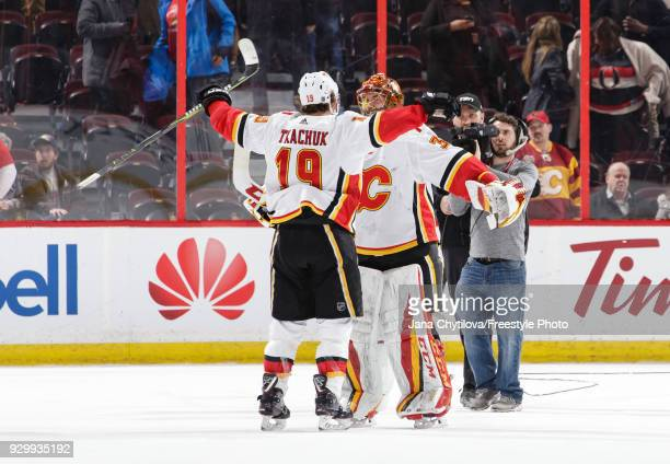 David Rittich of the Calgary Flames celebrate their win against the Ottawa Senators with teammate Matthew Tkachuk at Canadian Tire Centre on March 9...