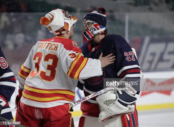 David Rittich of the Calgary Flames congratulates Connor Hellebuyck of the Winnipeg Jets following a 2-1 win during the 2019 Tim Hortons NHL Heritage...