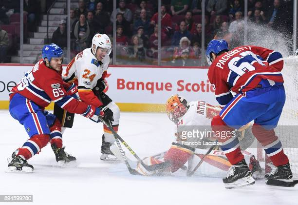 David Rittich of the Calgary Flames covers up the puck with help from Travis Hamonic under pressure from Andrew Shaw of the Montreal Canadiens in the...