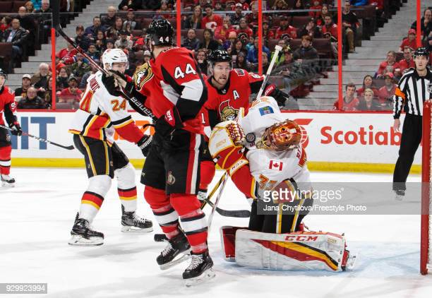 David Rittich of the Calgary Flames has the puck go off his facemask as JeanGabriel Pageau and Mark Stone of the Ottawa Senators look for the rebound...