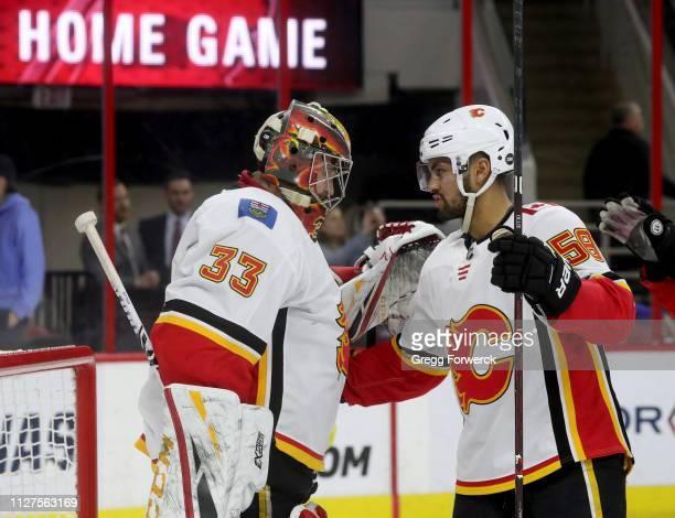 David Rittich of the Calgary Flames is congratulated by teammate Oliver Kylington after a victory over the Carolina Hurricanes during an NHL game on...