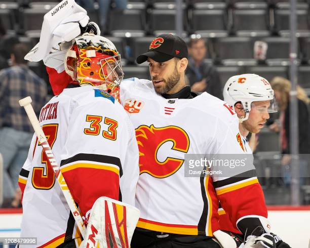 David Rittich of the Calgary Flames is congratulated by teammate Cam Talbot after an NHL game against the Detroit Red Wings at Little Caesars Arena...