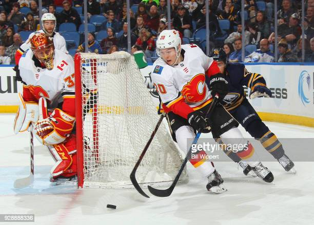 David Rittich of the Calgary Flames looks on as Curtis Lazar skates with the puck from behind the net against Scott Wilson of the Buffalo Sabres...