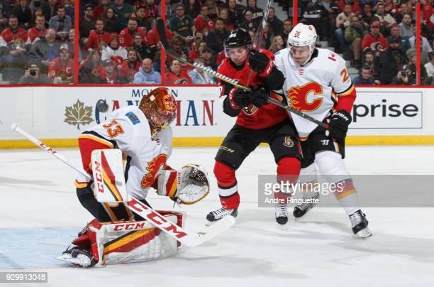 David Rittich of the Calgary Flames makes a save as Matt Duchene of the Ottawa Senators drives to the net for a rebound against Michael Stone at...