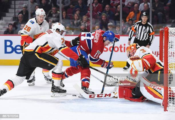 David Rittich of the Calgary Flames makes a save in front of Brendan Gallagher of the Montreal Canadiens in the NHL game at the Bell Centre on...