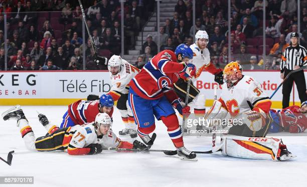 David Rittich of the Calgary Flames makes a save in front of Phillip Danault of the Montreal Canadiens in the NHL game at the Bell Centre on December...