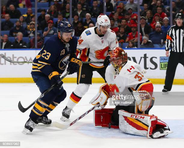 David Rittich of the Calgary Flames makes the save against Sam Reinhart of the Buffalo Sabres as Travis Hamonic looks on during the second period at...