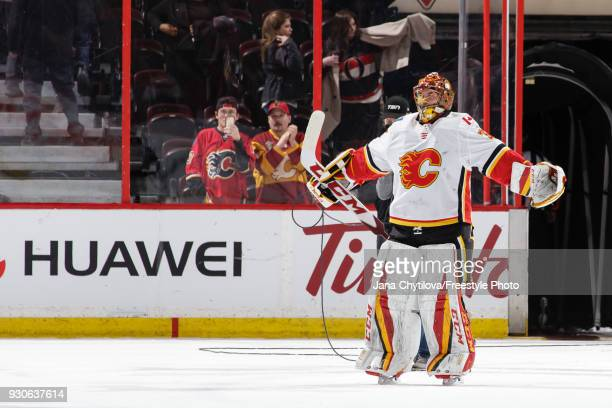 David Rittich of the Calgary Flames skates towards a teammate as he celebrates their win against the Ottawa Senators at Canadian Tire Centre on March...