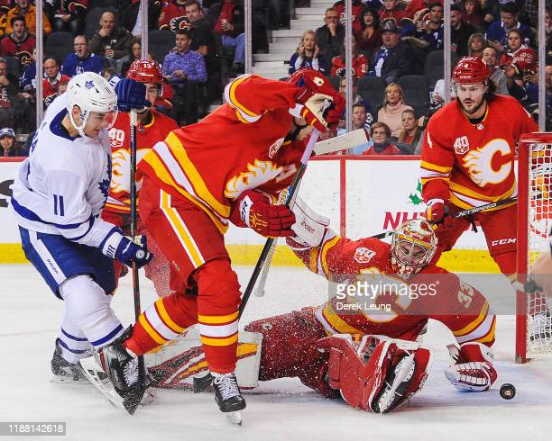 David Rittich of the Calgary Flames stops a shot from Zach Hyman of the Toronto Maple Leafs during an NHL game at Scotiabank Saddledome on December...