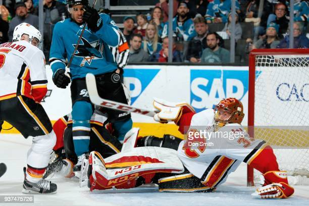 David Rittich of the Calgary Flames takes a fall while protecting the net as Evander Kane of the San Jose Sharks looks at SAP Center on March 24 2018...