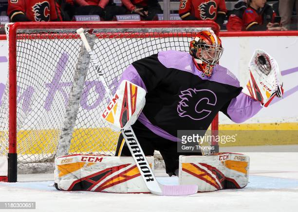 David Rittich of the Calgary Flames warms up as he and teammates wear special Hockey Fights Cancer jerseys before an NHL game against the Arizona...