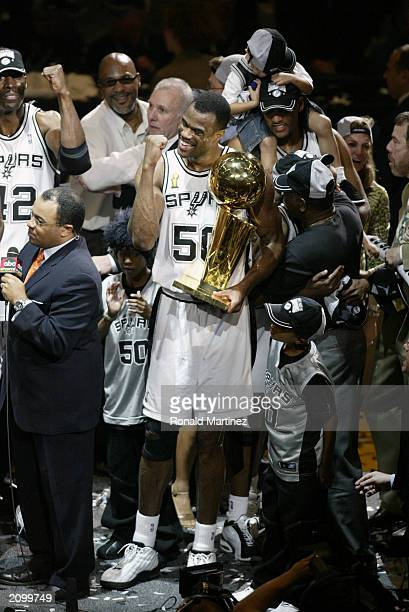 David Robinson of the San Antonio Spurs celebrates as he holds the 2003 NBA Championship trophy during the post game celebration after defeating the...